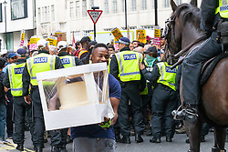 """A man struggles through a near riot with a wedding cake he is delivering to the Langham Hotel as several hundred protesters in central London demand the release of """"political prisoner"""" right wing talisman Stephen Yaxley-Lennon  - also known as Tommy Robinson, who was imprisoned for contempt of court. London, August 03 2019."""