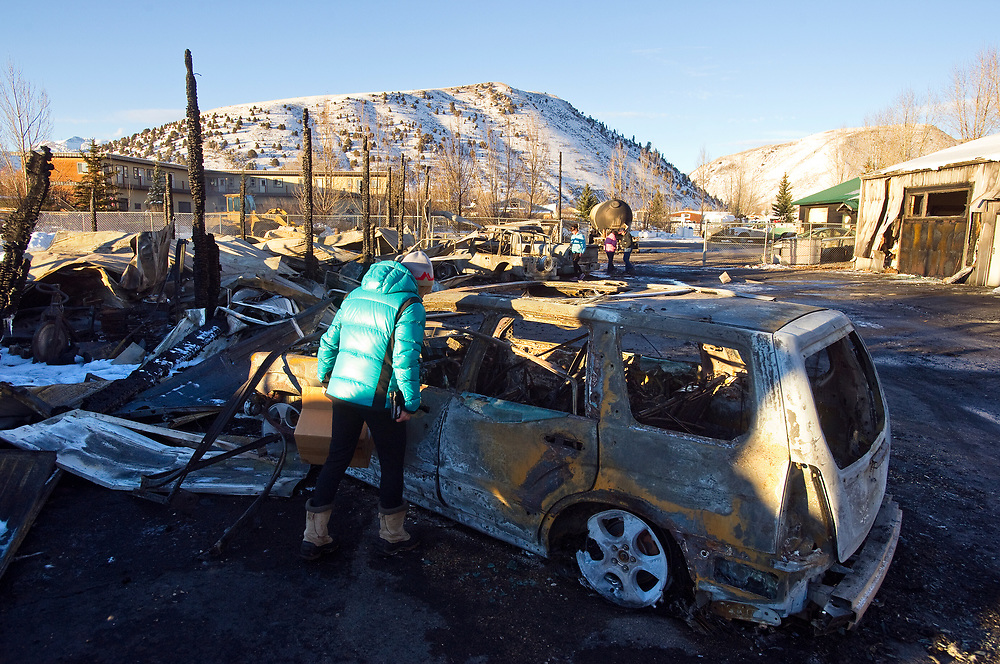 Vicky O'Donaghue inspects the melted frame of her Subaru Forester on Friday in the parking lot of Bell Fitness, where she was exercising Thursday as a gas explosion at Amerigas caught numerous vehicles and several buildings on fire. The blaze burned so hot it melted the rims of the car.