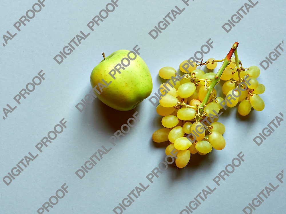 Green apple and bunch of green grapes isolated in studio against a grey background viewed from above