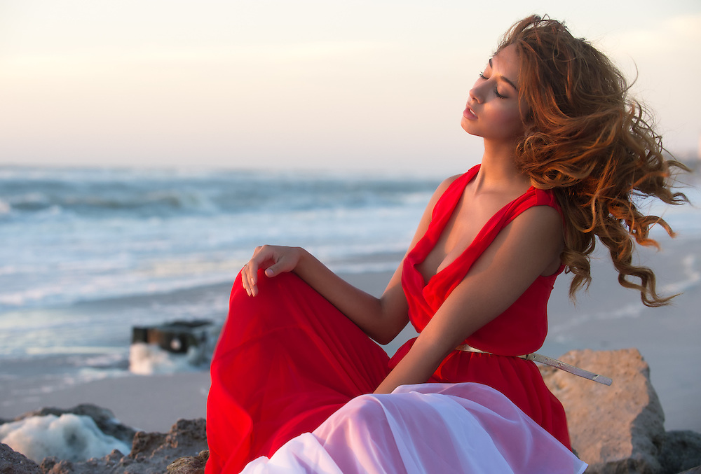 Young woman relaxing on the beach during sunset