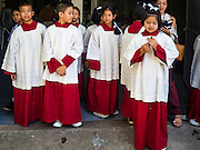 18 SEPTEMBER 2016 - BANGKOK, THAILAND:  Alter servers at Santa Cruz church wait for the church's 100th anniversary mass to start. Santa Cruz Church was establised in 1769 to serve Portuguese soldiers in the employ of King Taksin, who reestablished the Siamese (Thai) empire after the Burmese sacked the ancient Siamese capital of Ayutthaya. The church was one of the first Catholic churches in Bangkok and is one of the most historic Catholic churches in Thailand. The first sanctuary was a simple wood and thatch structure and burned down in the 1800s. The church is in its third sanctuary and was designed in a Renaissance / Neo-Classical style. It was consecrated in September, 1916. The church, located on the Chao Phraya River, serves as a landmark for central Bangkok.      PHOTO BY JACK KURTZ