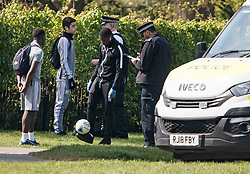 **EDITORS NOTE: people pictured possibly under the age of 16**<br /> © Licensed to London News Pictures. 15/04/2020. London, UK. A group of young paying football in Primrose Hill, North London, being stopped and searched by police officers, during a pandemic outbreak of the Coronavirus COVID-19 disease. The public have been told they can only leave their homes when absolutely essential, in an attempt to fight the spread of coronavirus COVID-19 disease. Photo credit: Ben Cawthra/LNP