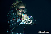 marine biologist Sarah Matye records sightings on a slate during a blackwater dive in the surface waters of the deep open ocean at night, Kona, Hawaii, USA ( Central Pacific Ocean ) MR 479