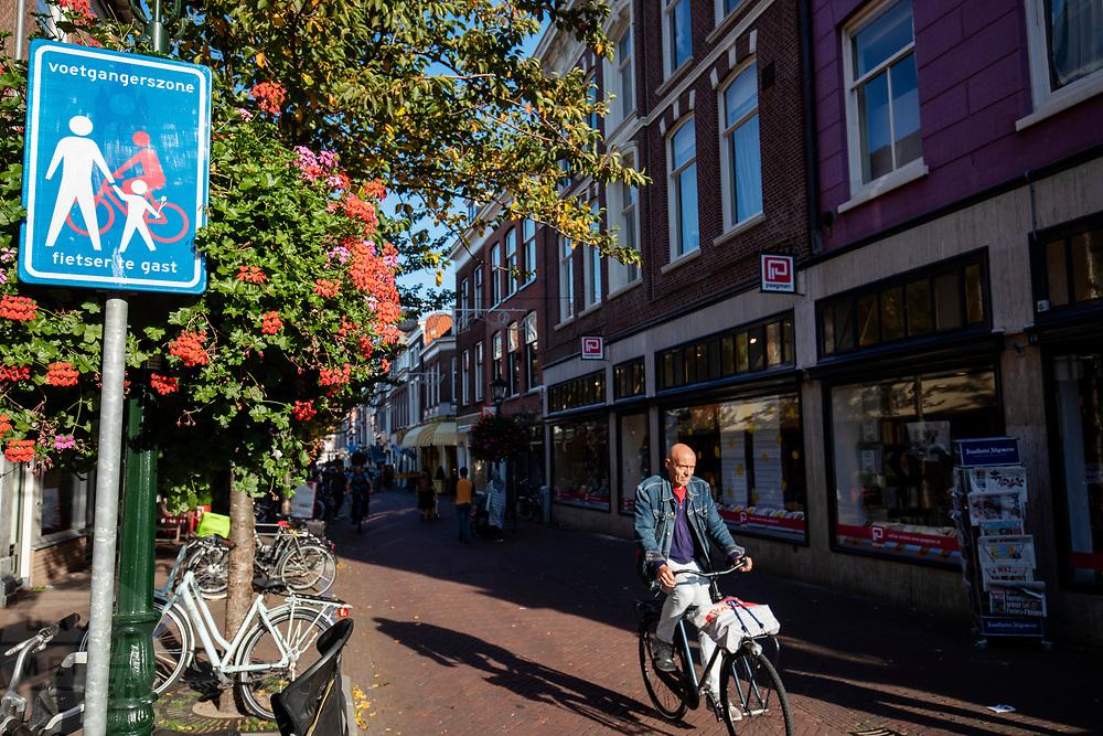 In Delft rijden fietsers door de voetgangerszone waar fietsen te gast zijn.<br /> <br /> Cyclist ride in the pedestrian zone in Delft.