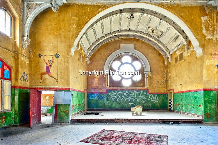 Duitsland, Beelitz, 28-3-2014 Het vervallen sanatorium Heilstätten Beelitz in Brandenburg, Duitsland. Het sanatorium is gebouwd rond 1900 als TBC kliniek. Tijdens de eerste wereldoorlog is het in gebruik als een militair hospitaal. In October en November 1916, verbleef Adolf Hitler hier omdat hij herstelde van een beenwond opgelopen tijdens de Slag aan de Somme. Tot de val van de muur in 1989 werd het complex gebruikt als hospitaal voor de Sovjet militairen. In 1990 werd Erich Honnecker hier behandeld voor leverkanker. Maar hij moest al snel vertrekken naar Moskou om opsluiting in Duitsland te voorkomen. De gebouwen staan al jaren te verpauperen. Een Berlijnse bouwmagnaat kocht het complex in 1994 en knapte een van de hoofdgebouwen op, welk nog steeds in gebruik is.. Hij had zich echter in het project verslikt en ging in 2001 failliet. In 2008 verwierf een Potsdammer architect het terrein uit de boedel en zoekt sindsdien naar een investeerder. Tot nog toe tevergeefs, terwijl de gebouwen door natuur en vandalisme langzaam gesloopt worden. Foto: Flip Franssen