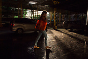 Woman walking under a scaffolding structure on Palm Drive, Makati in Manila, Philippines. (photo by Andrew Aitchison / In pictures via Getty Images)