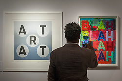 """© Licensed to London News Pictures. 29/06/2017. London, UK.  A man photographs (L to R) """"Art"""", 2013, by Robert Indiana and """"Blah, Blah Blah"""", 2017, by Mel Blochner.  Members of the public visit Masterpiece London, a leading art fair held in the grounds of the Royal Hospital Chelsea.  The fair brings together 150 international exhibitors presenting works from antiquity to the present day and runs 29 June to 5 July 2017.  Photo credit : Stephen Chung/LNP"""