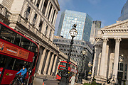 Days before the Chancellor Rishi Sunak delivers his Budget, buses queue at red lights with a wide view of the Bank of England (left) and Royal Exchange (right) in the City of London, the capital's financial district, on 1st March 2021, in London, England.