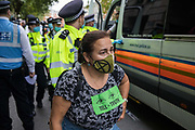 Metropolitan Police officers arrest an activist from HS2 Rebellion, an umbrella campaign group comprising longstanding campaigners against the HS2 high-speed rail link as well as Extinction Rebellion activists, after she sat in the road outside the Department for Transport during a protest on 4 September 2020 in London, United Kingdom. Activists glued themselves to the doors and pavement outside the building and sprayed fake blood around the entrance during a protest which coincided with an announcement by HS2 Ltd that construction of the controversial £106bn high-speed rail link will now commence.