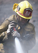 A firefighter douses the hot spots from a wildfire, Monday, Sept. 4, 2017, in the Sunland-Tujunga of Los Angeles, the United States, on Sept. 4, 2017. More than 1,000 firefighters work for a fourth day to put out a 7,000-acre brushfire that is 30 percent contained, as the last of the residents ordered to evacuate the record-setting blaze were expected to return to their homes authorities said. (Xinhua/Zhao Hanrong)(Photo by Ringo Chiu)<br /> <br /> Usage Notes: This content is intended for editorial use only. For other uses, additional clearances may be required.