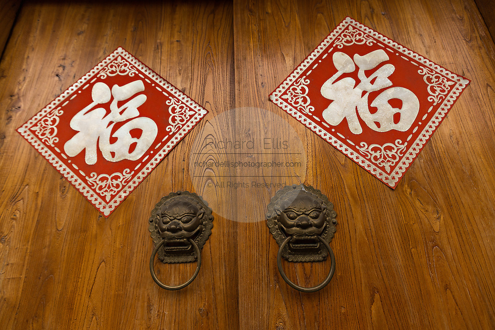 Traditional Chinese door with red lanterns and good luck signs  in the restored hutong district of Wudaoying in Beijing, China