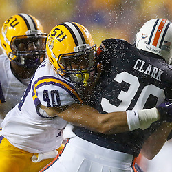 Sep 21, 2013; Baton Rouge, LA, USA; Auburn Tigers punter Steven Clark (30) is tackled by LSU Tigers linebacker Duke Riley (40) after fumbling a punt attempt during the first quarter of a game at Tiger Stadium. Mandatory Credit: Derick E. Hingle-USA TODAY Sports
