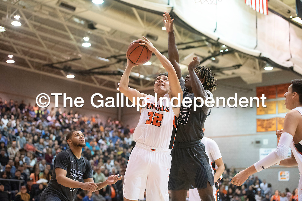 Gallup's Johnny Blueeyes (32) takes a shot under the basket as Spring Valley's James Webster (23) defends Saturday night at the Gallup Invitational boys basketball tournament at Gallup High School.