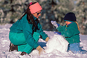 Mother and child (age 3) building a snowman, Los Padres National Forest, California USA