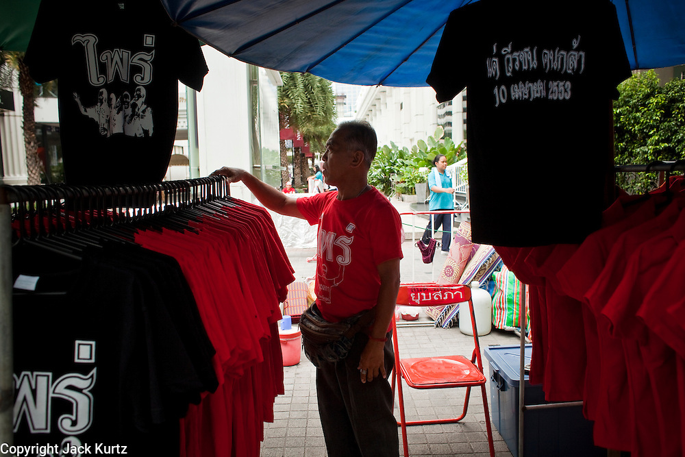 18 APRIL 2010 -- BANGKOK, THAILAND: A Red Shirt tee shirt vendor sets up his stand near the protest site in central Bangkok. The Red Shirts protest in the Ratchaprasong Shopping district, home to Bangkok's most upscale malls, is costing the Thai economy millions of Baht per day because the malls and most of the restaurants are closed and tourists are staying away from the area. But that hasn't stopped the Red Shirts who have brought their own economy with them. There are Red Shirt restaurants, food stands, souvenir vendors and more, creating a micro economy for Red Shirts in the area.  The Red Shirts continue to occupy Ratchaprasong Intersection an the high end shopping district of Bangkok. They are calling for Thai Prime Minister Abhisit Vejjajiva to step down and dissolve the parliament. Most of the Red Shirts support ousted former Prime Minister Thaksin Shinawatra.   PHOTO BY JACK KURTZ