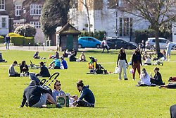 """© Licensed to London News Pictures. 29/03/2021. London, UK. Members of the public enjoy the sunshine in Richmond Green, South West London as weather forecasters predict highs of 23c in London and the South East this week as the """"Rule of Six"""" is reintroduced and marking the end of the """"Stay at Home"""" government advice. From today, Monday 29 March, two households or six people will be allowed to meet up. Playing golf, tennis and organised outdoor sports will also be allowed as England starts to unlock after a year of Covid-19 restrictions. Photo credit: Alex Lentati/LNP"""
