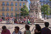 Tourists sit to listen to a guide talking during a tour of central Lisbon, Portugal.