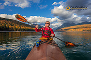 Sea kayaking in late autumn light on Bowman Lake in Glacier National Park, Montana, USA model released