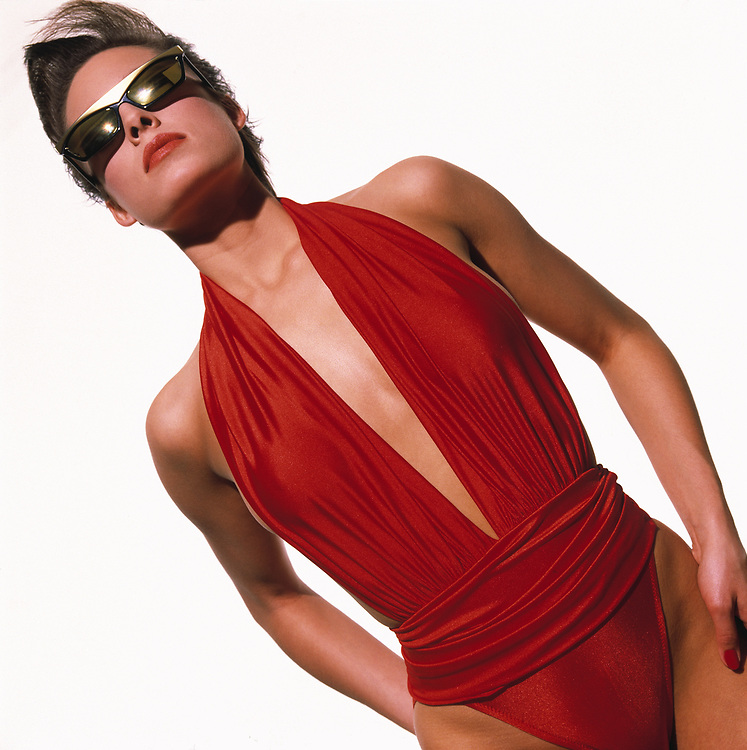 Woman in exotic red bathing suit and sunglasses looking at sun. She also has a contemporary hair style and is standing in front of a white background.