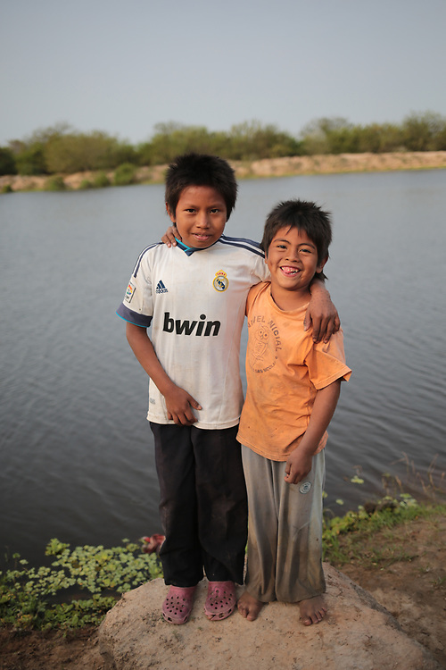 Children in an Enxet Sur indigenous village in the Gran Chaco, Paraguay.<br /> <br /> Until recently, the Enxet people survived entirely as nomadic hunter, fisher gatherers. But as commercial farming has encroached dramatically on their traditional lands, they are now living in a reduced area of land, very small by Paraguayan farming standards, unable to move as they did between hunting and fishing grounds, and according to seasons for gathering in the forests. They are finding it hard adapting to the changes. While they still survive mainly by hunting and fishing, their diet, nutrition and food security has suffered. They live in very remote areas, and buying food is from travelling salesmen called 'macateros' is difficult because they are so overpriced and their incomes, from occasional labour on nearby farms, are so low.<br /> <br /> Church World Service supports the community by teaching them to grow vegetables for themselves and providing the seeds for community vegetable gardens. Despite setbacks from floods and droughts, the projects have been taken up enthusiastically by the indigenous people.