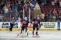 KELOWNA, BC - SEPTEMBER 21:   Referee Sean Raphael calls the goal good and Roman Basran #30 and Kyle Topping #24 of the Kelowna Rockets celebrate the overtime win against the Spokane Chiefs at Prospera Place on September 21, 2019 in Kelowna, Canada. (Photo by Marissa Baecker/Shoot the Breeze)
