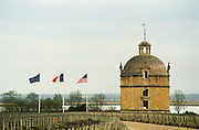 Chateau Latour, the tower that has given its name to the chateau, with a view of the river Gironde in the background, three flag poles flagpoles with the flags of the European Union, France and the United States of America USA, Pauillac France Médoc Bordeaux Medoc Bordeaux Gironde Aquitaine France Europe