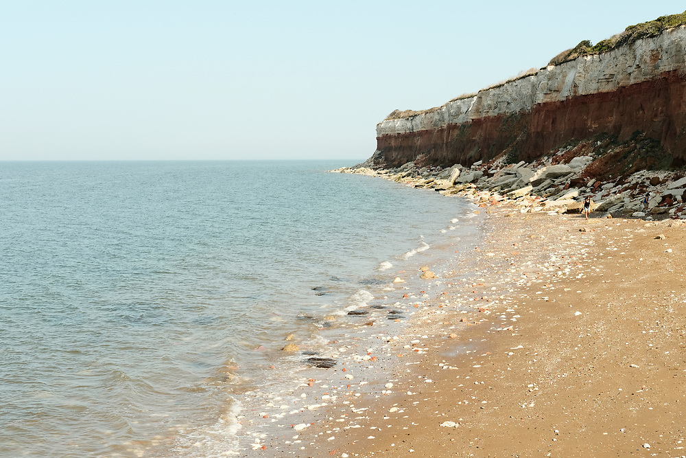 The famous red and white striped cliffs at Hunstanton, tourists climb along the edge & enjoy the sea side.<br /> Taken on the last hot day of the Summer in Hunstanton Norfolk, the first summer in the UK during the COVID-19 pandemic.<br /> <br /> Photo by Jonathan J Fussell, COPYRIGHT 2020