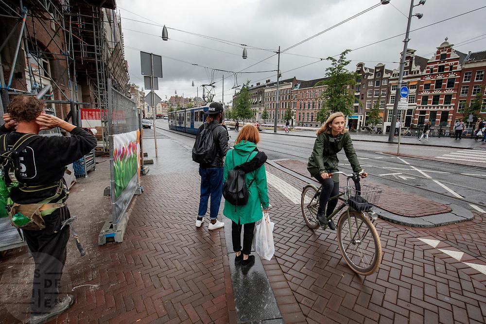Een vrouw rijdt op het Rokin in Amsterdam langs een bouwplaats.<br /> <br /> A woman passes a construction area at the Rokin in Amsterdam.