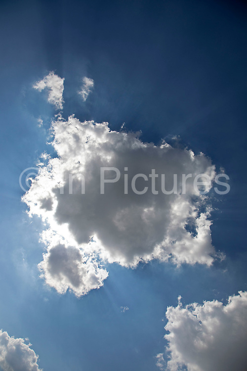 Heavenly shafts of light as sunlight creates shadow from behind a cloud at Broadway in The Cotswolds, United Kingdom. Particles in the air are picked up by the sun rays making a haze from behind the clouds.