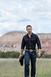 rugged cowboy walking on a ranch