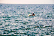 A fisherman rows out to sea in a small dinghy