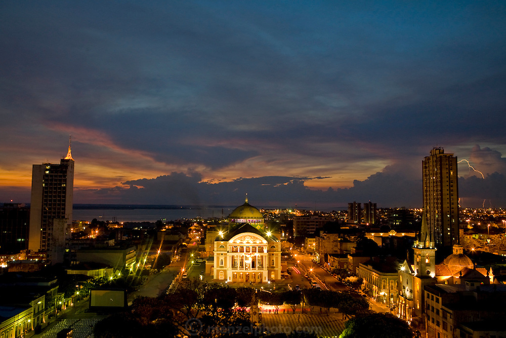 Lights illuminate the Amazon Theater in Manaus, Brazil at dusk as a lightning storm flashes over the Solimoes River. The opera house was built in eclectic neo-classic style during the rubber boom period in the 1890's.