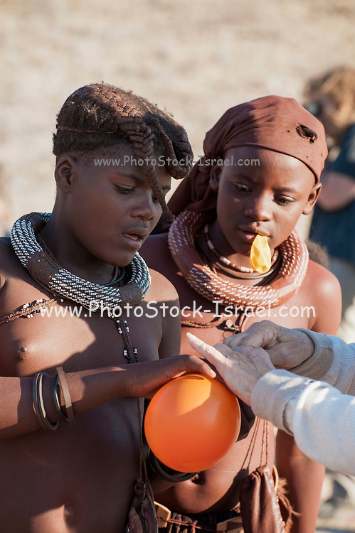 Young Himba teens are given balloons by well wishing European tourists, Namibia, Africa