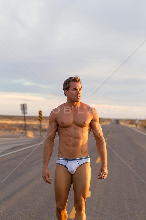 sexy man in tighty whitey briefs on a road in the desert