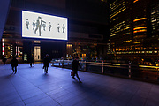 Salarymen walk past a screen at Akihabara UDX building in Akihabara, Tokyo, Japan. Monday January 4th 2021