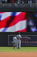 Aaron Hicks #32 of the Minnesota Twins stands with a young fan during the national anthem before a game against the Seattle Mariners on June 2, 2013 at Target Field in Minneapolis, Minnesota.  The Twins defeated the Mariners 10 to 0.  Photo: Ben Krause