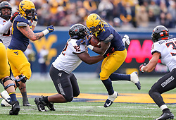 Nov 23, 2019; Morgantown, WV, USA; West Virginia Mountaineers running back Leddie Brown (4) runs the ball and is tackled by Oklahoma State Cowboys defensive tackle Jayden Jernigan (42) during the second quarter at Mountaineer Field at Milan Puskar Stadium. Mandatory Credit: Ben Queen-USA TODAY Sports