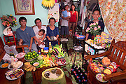 The Cabaña family in the main room of their 200-square-foot apartment in Manila, the Philippines, with a week's worth of food. Seated are Angelita Cabaña, 51, her husband, Eduardo Cabaña, 56 (holding sleeping grandson Dave, 2), and their son Charles, 20. Eduardo, Jr., 22 (called Nyok), his wife Abigail, 22, and their daughter Alexandra, 3, stand in the kitchen. Behind the flowers is the youngest son, Christian, 13 (called Ian). The Cabaña family is one of the thirty families featured in the book Hungry Planet: What the World Eats (MODEL RELEASED IMAGE).