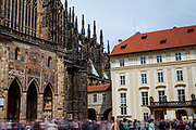 Tourist groups and visitors passing the third courtyard of Prague Castle. On the left  St. Vitus Cathedral. This cathedral is a prominent example of Gothic architecture and is the largest and most important church in the country.
