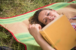 Woman reading a book lying on picnic blanket on meadow, Bavaria, Germany