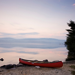 A canoe on the shoreline of Lake Sunapee at sunrise at Mount Sunapee State Park in Newbury, New Hampshire.
