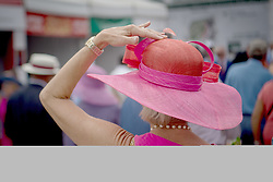 May 4, 2018 - Louisville, Kentucky, U.S. - A woman holds on to her Derby Hat on Kentucky Oaks Day at Churchill Downs in Louisville, Ky, May 4, 2018. (Credit Image: © Bryan Woolston via ZUMA Wire)