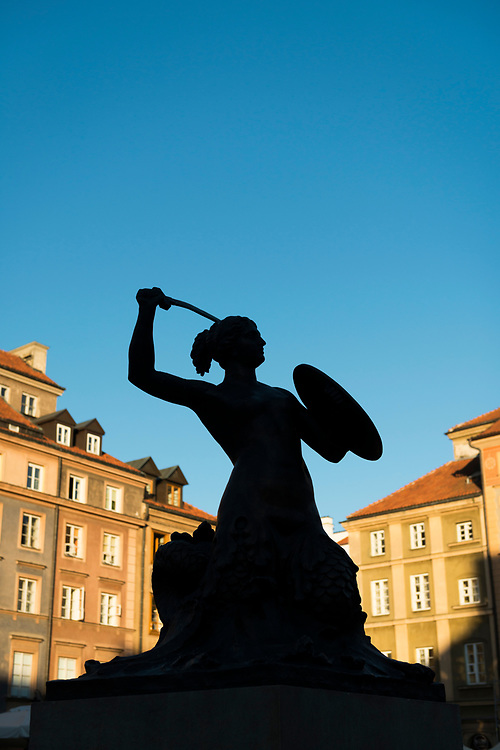 The landmark mermaid sculpture in the old town of Warsaw, Poland. Silhouetted in the late afternoon light.