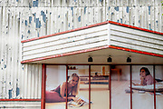 A dystopian lifestyle landscape showing beautiful women reclining on the floors of the aspirational homes, at the entrance of a retail park business in Canning Town, Newham, on 11th August 2021, in London, England.