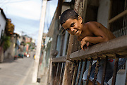 A boy looks down from the verandah of his home in Santiago, Cuba on Wednesday July 9, 2008.