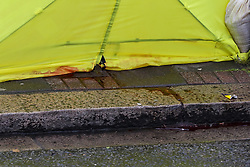 © Licensed to London News Pictures. 09/04/2019. London, UK. Blood stains at the bottom of the police tent and the pavement on Church Road, Manor Park, East London where a man in his 20s was shot and stabbed to death on Monday 8 April 2019. Police were called around 9.30pm and the man was found with knife and gunshot wounds. The victim was pronounced dead at the scene. Photo credit: Dinendra Haria/LNP