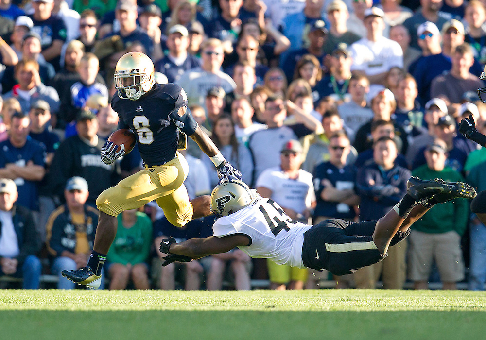 September 08, 2012:  Notre Dame Fighting Irish running back Theo Riddick (6) turns the corner on the run as Purdue linebacker Will Lucas (45) attempts to make diving tackle during NCAA Football game action between the Notre Dame Fighting Irish and the Purdue Boilermakers at Notre Dame Stadium in South Bend, Indiana.  Notre Dame defeated Purdue 20-17.