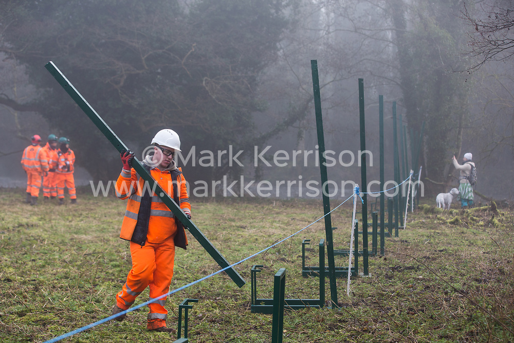 Denham, UK. 6 February, 2020. An environmental activist observes engineers working on behalf of HS2 as they construct a security fence at Denham Ford. Works planned for the HS2 high-speed rail link in the immediate vicinity include the construction of a Bailey bridge across the ford and a compound in Denham Country Park requiring the felling of mature trees. Some of the site lies within a wetland nature reserve forming part of a Site of Metropolitan Importance for Nature Conservation (SMI).