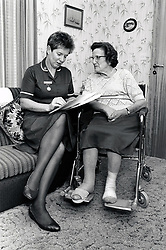 District nurse visiting elderly woman at home, Nottingham UK 1991