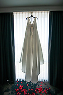 A bride's wedding dress hangs in the window before the ceremony. Photo by Kristina Cilia Photography